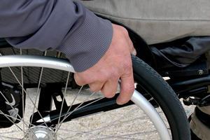 main sur la roue d'un fauteil roulant